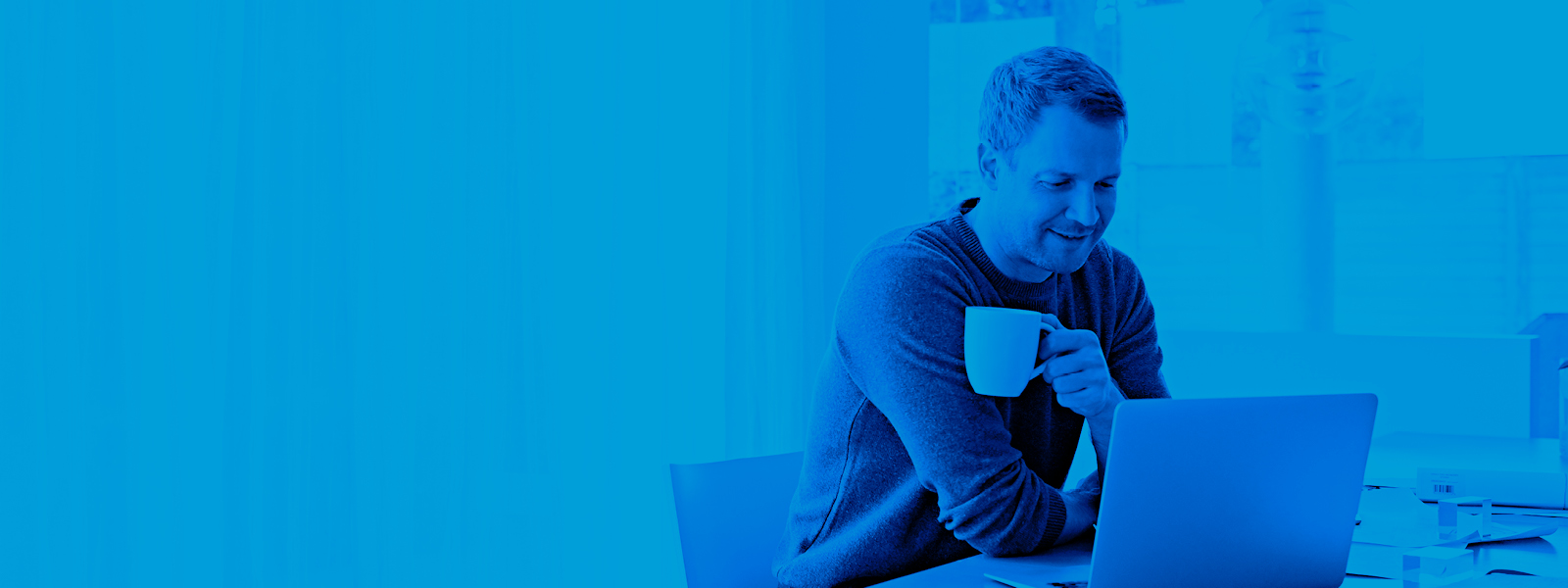 Imagen de un hombre tomando café mientras trabaja